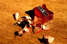 red plastic pencil sharpener with shavings on a wooden table