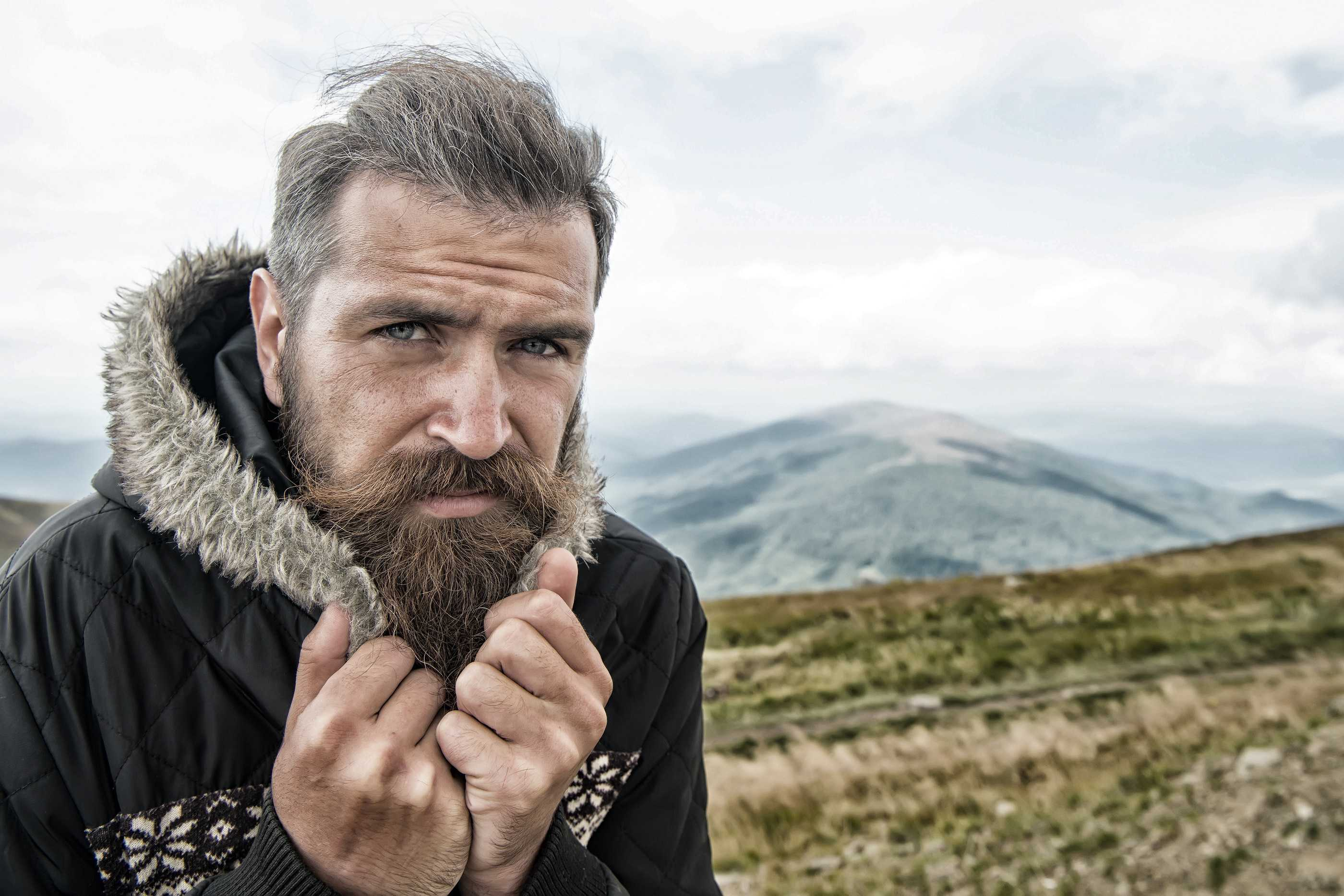 Hipster with serious face at mountains. Guy or bearded man at cold weather.